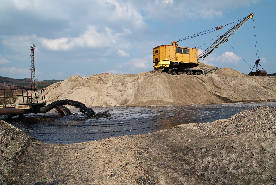 Rope excavator for mining sludge among piles of sand, black sludge polluted water gushing from a pipe, black stream polluted water, environmental pollution